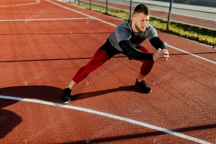 Close up photo of man is stretching outdoors, representing healthy active lifestyle model.