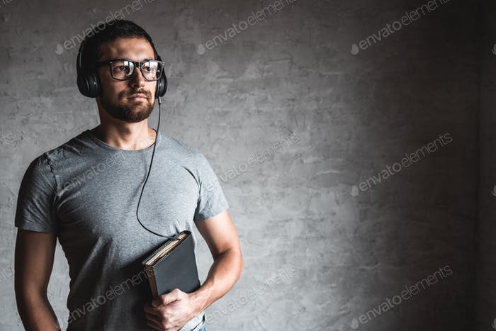 Portrait stylish bearded man dressed in grey casual t-shirt listening audio book with his earphones