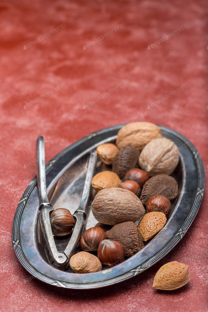 Hazelnut, walnut, almond and brazil nuts on plate with nut cracker, vertical, copy space