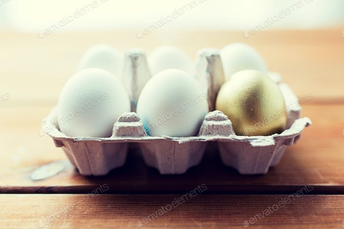 close up of white and gold eggs in egg box