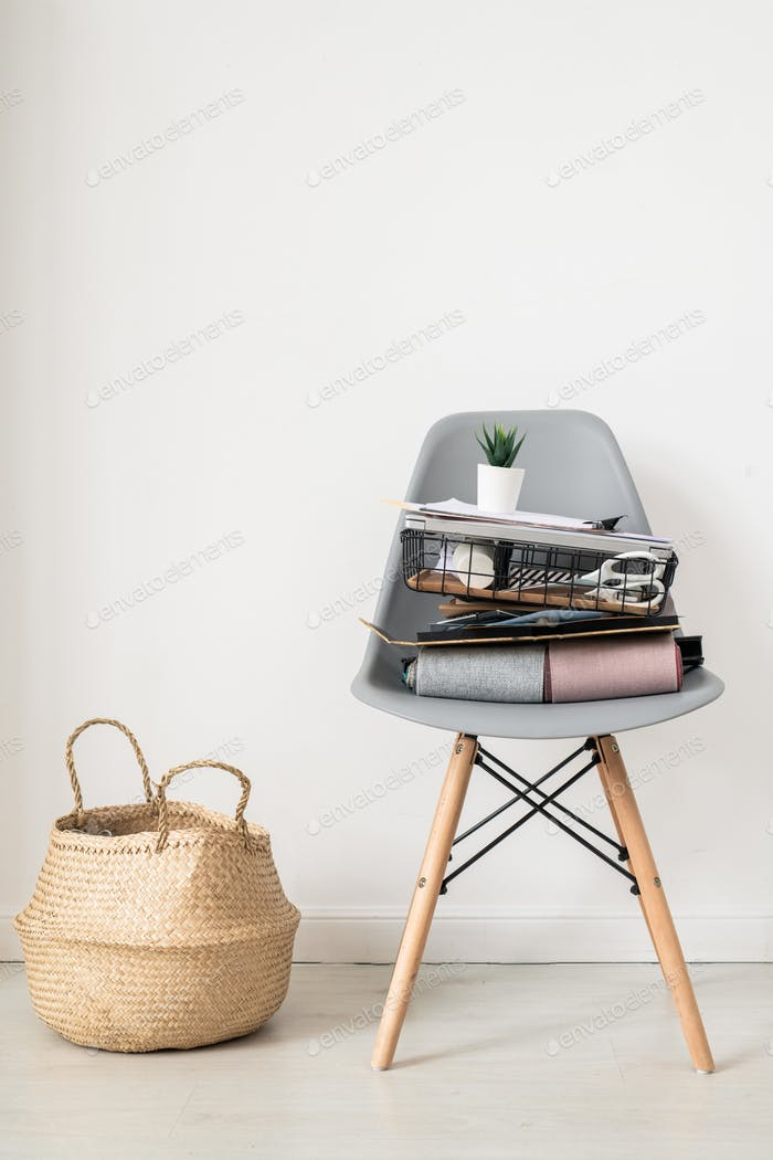 Grey plastic chair with stack of textile samples, office supplies and flowerpot