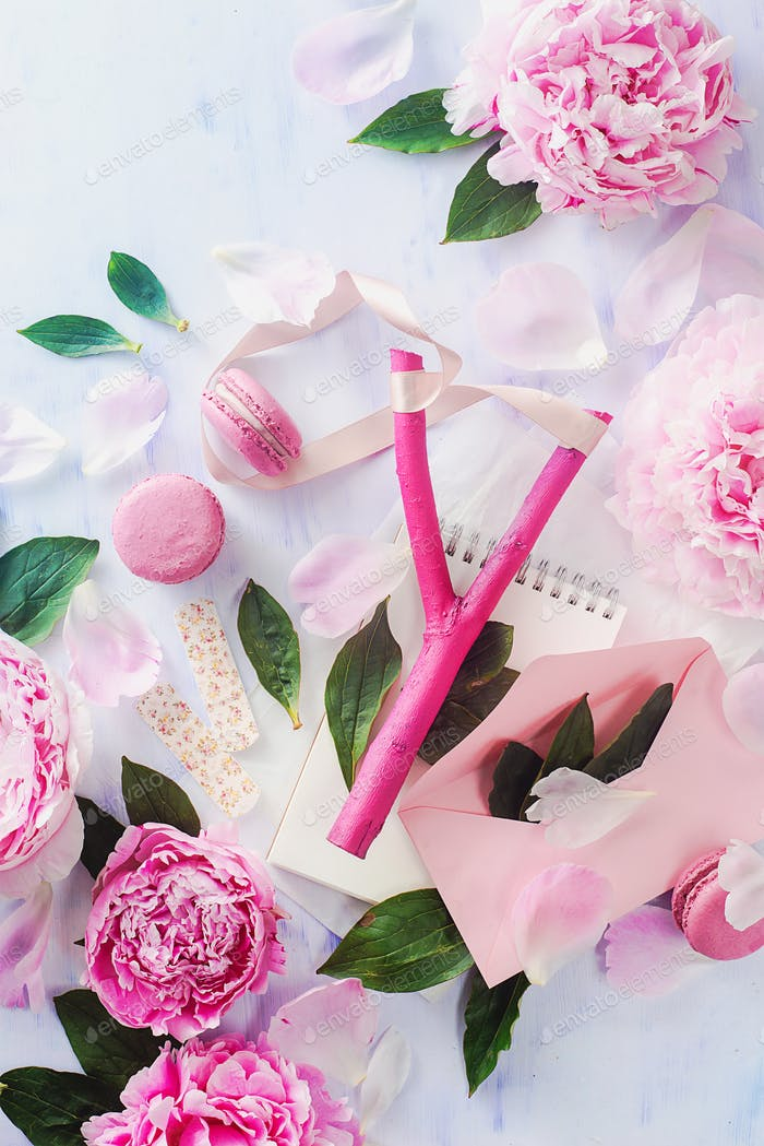 Bright pink slingshot with macarons, a love letter and peony flowers