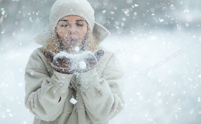 Beautiful woman blowing snow in the snowy park