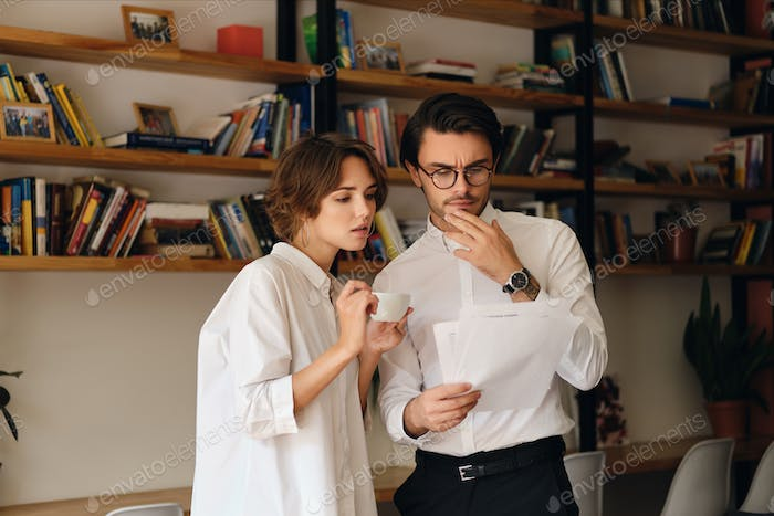 Pensive business colleagues with documents thoughtfully discussing work together in office