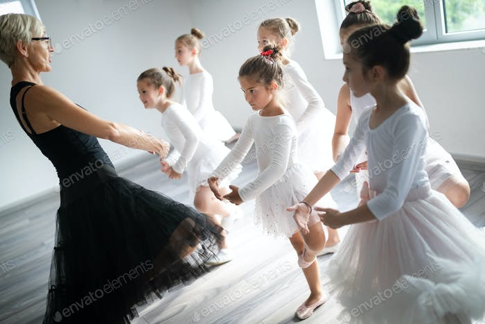 Ballet teacher and group of children ballerinas exercising in ballet studio