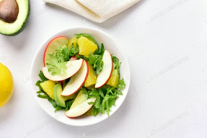 Healthy salad with red apples, avocado, orange slices