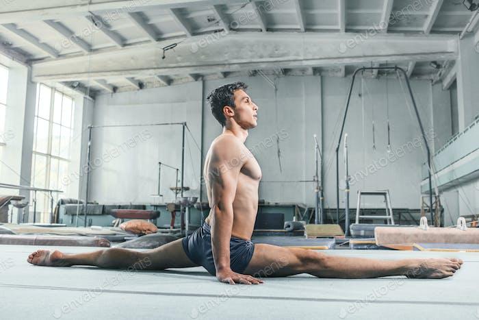 Hombre caucásico acrobacias gimnasia equilibrio postura en el Fondo del gimnasio