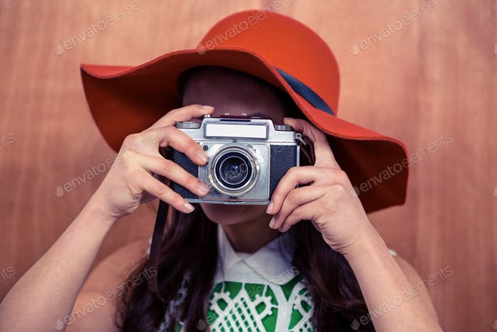 Woman with hat taking photograph with camera against wooden wall