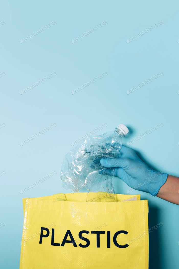 Hand in blue gloves puts plastic bottle in recycling bin. Environment care, sorting waste. Copy