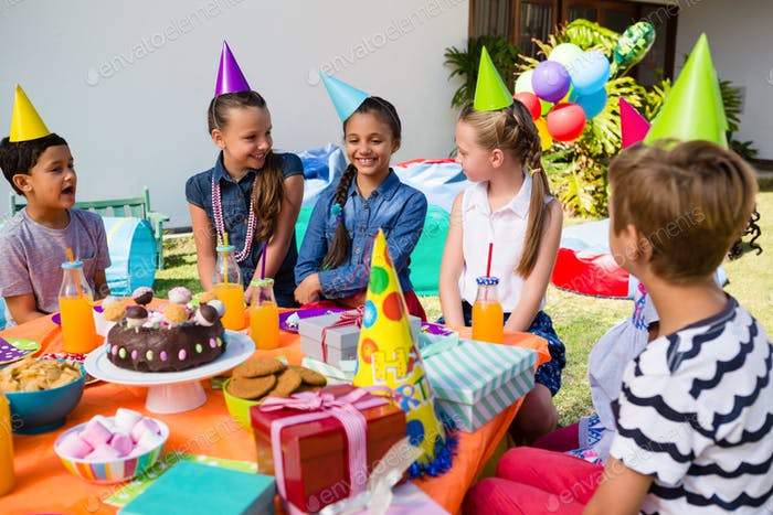 Happy children talking at table in yard