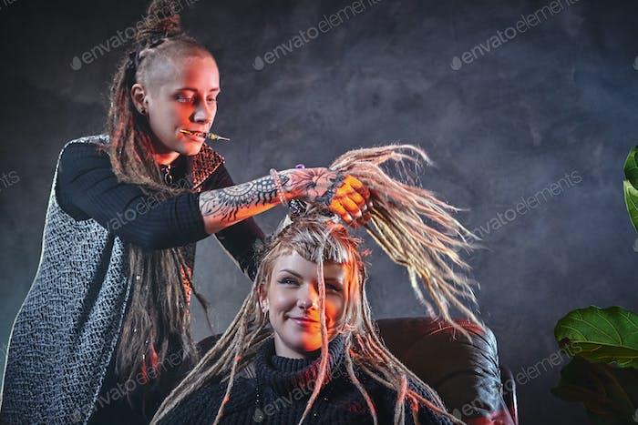 Dreadlocks master is working on client's head
