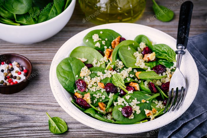 Green salad bowl with spinach, quinoa, walnuts and dried cranberries