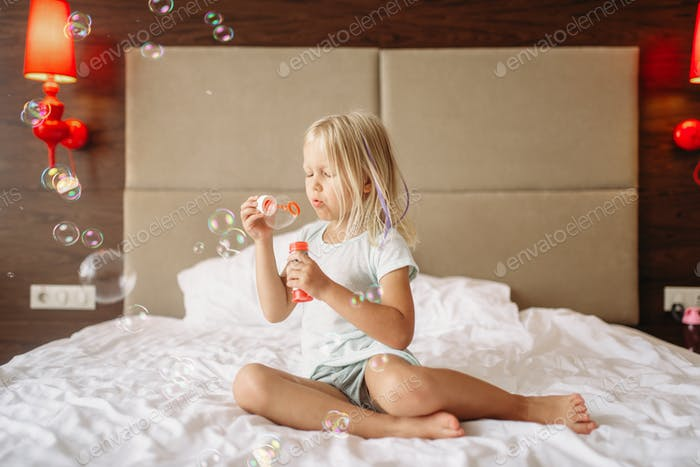 Little girl lying in bed and blowing bubbles