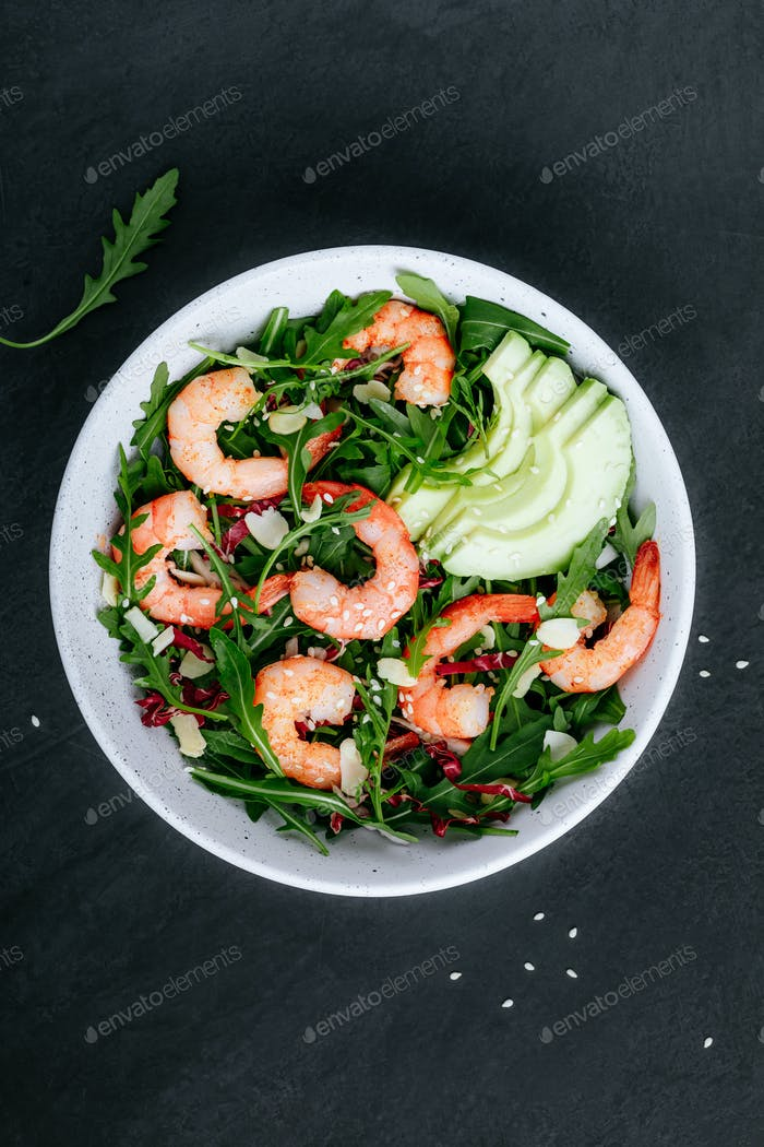 Shrimp salad with fresh green arugula leaves and avocado, radicchio, almond and sesame seeds.