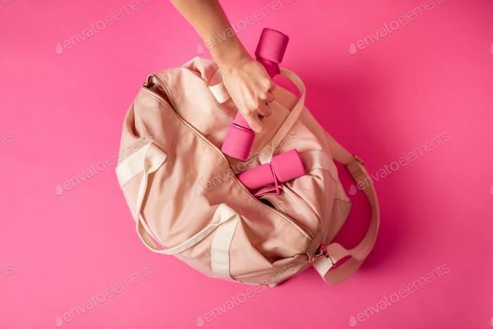 Damen Sporttasche mit Hanteln liegend auf rosa Hintergrund