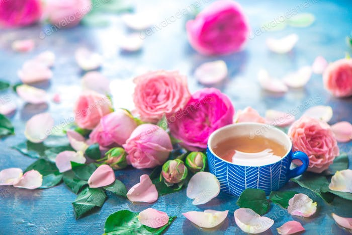 Rose tea photography with ceramic teacups and flower petals on a wet light background with copy
