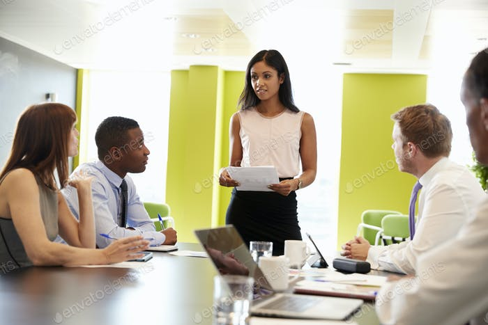 Female boss stands holding document at informal work meeting