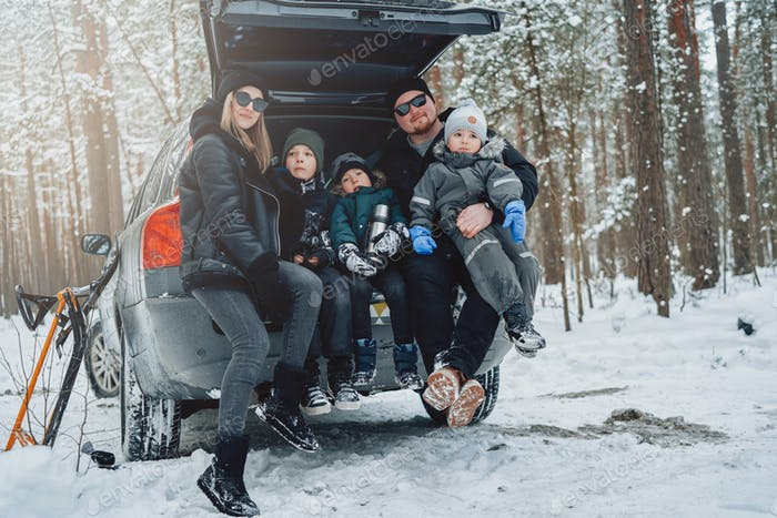 Caucasian family dressed in warm clothing in winter forest