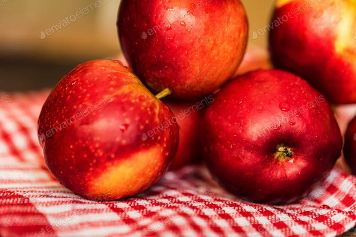 Whole ripe red apples on checked tablecloth close