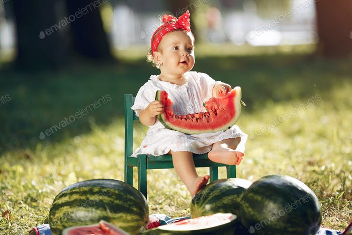 Cute little girl with watermelons in a park