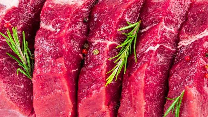 background of fresh raw sliced beef steaks, garlic, rosemary and seasonings. Juicy meat banner