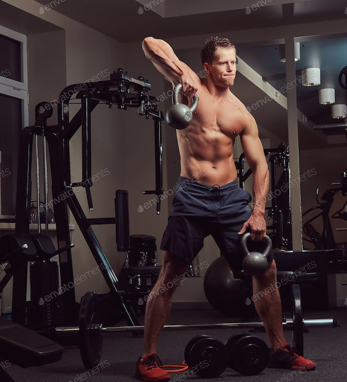 Handsome muscular shirtless bodybuilder male doing exercises with a dumbbell in the gym.
