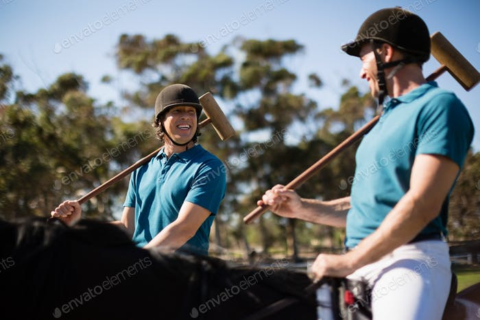 Two male jockeys riding horse in the ranch