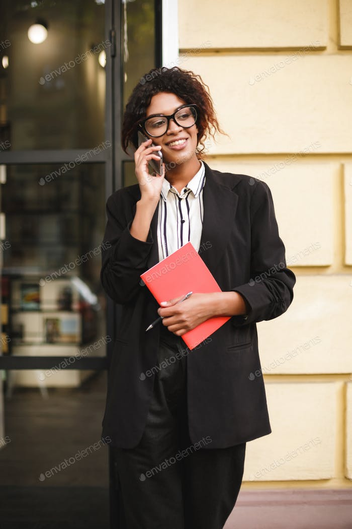 African American girl in glasses standing near door happily looking aside talking on her cellphone