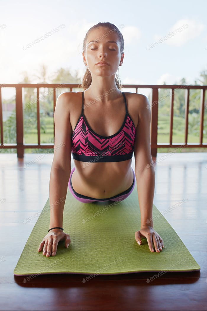 Fitness woman doing cobra pose yoga