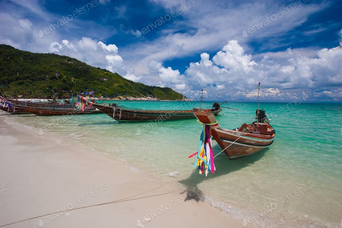 Picture of empty long tail boat on tropical beach. Clear water and blue sky with clouds. Horizontal