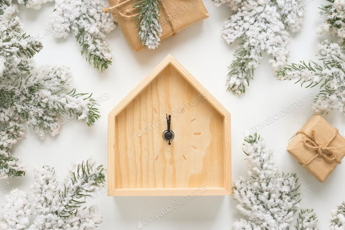 Christmas and New Year still life. Wooden clock shows five minutes to midnight.