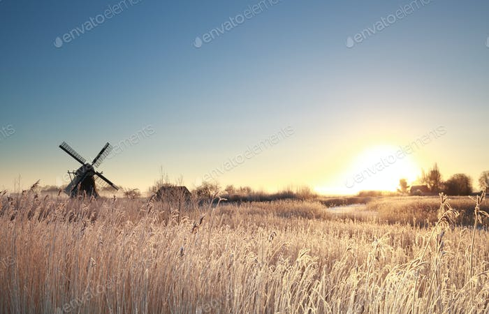 sunrise by windmill on frosty morning