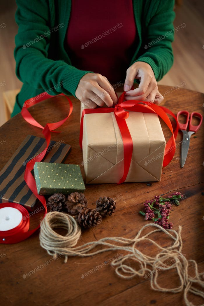 Woman decorating Xmas gift with red bow