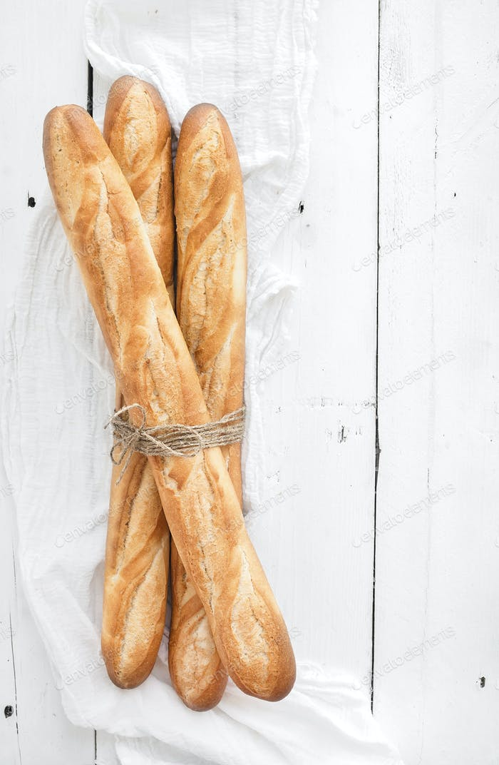 Freshly baked French baguettes on white wooden table. Top view