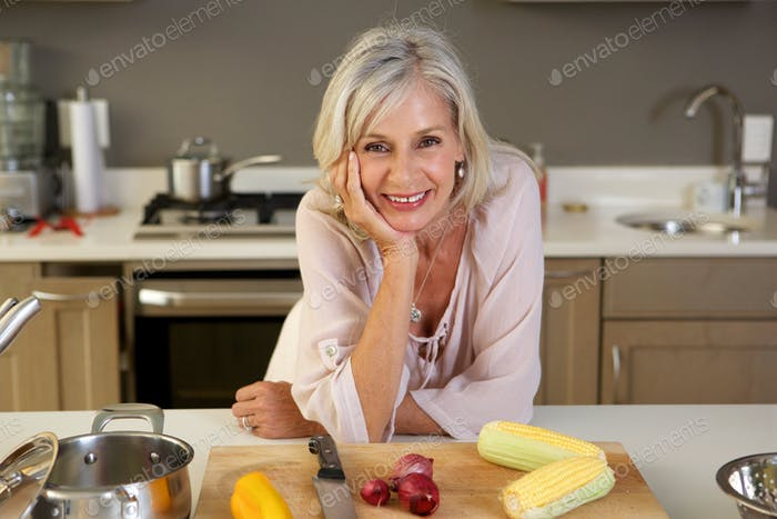 older beautiful woman leaning on kitchen counter with fresh produce