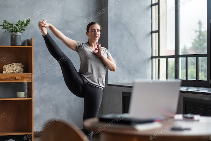 Flexible woman balancing doing asana Standing Hand to Toe at home.