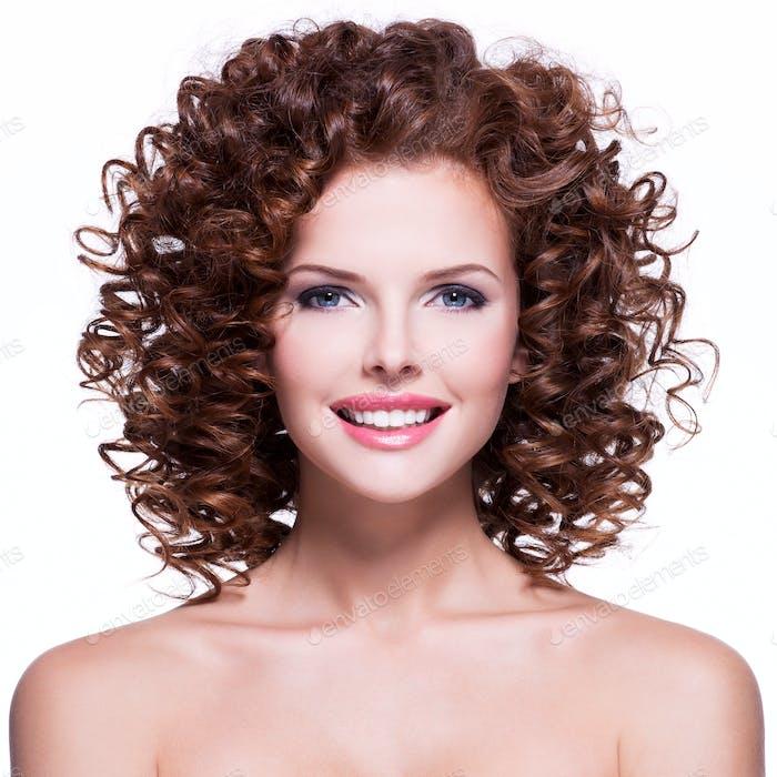 Schöne lächelnde Frau mit brünetten lockigen Haaren.