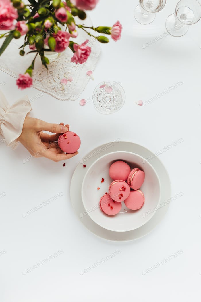 Woman's Hand Taking Strawberry Macaron from White Bowl