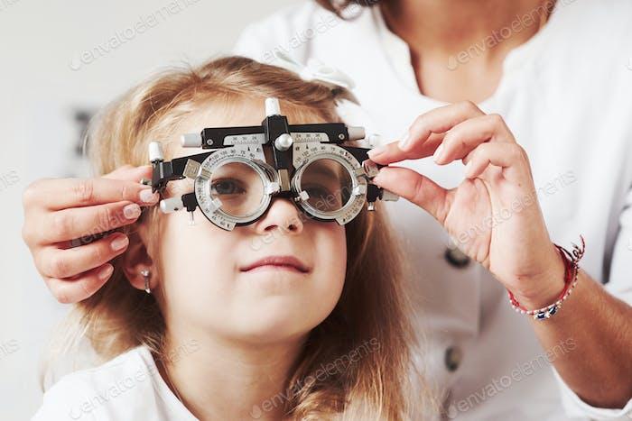 Schwierig, dieses Wort zu sehen. Arzt Überprüfung kleines Mädchen Anblick und Tuning der Phoropter
