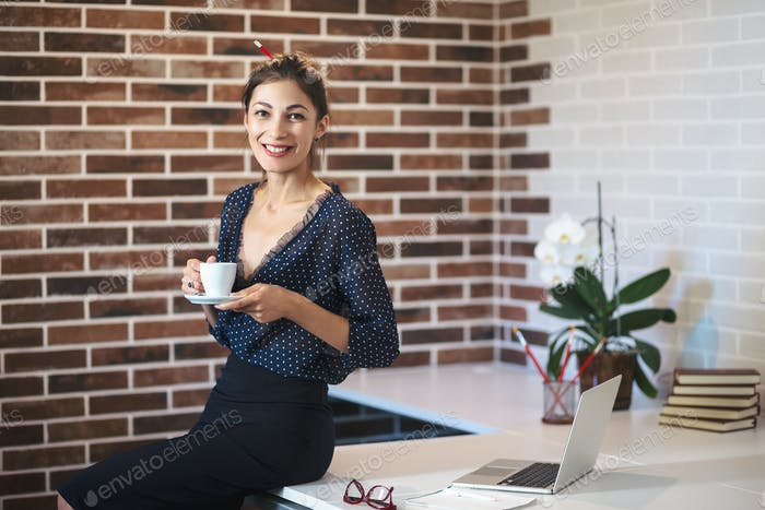 Happy woman sitting on the desk with a cup of coffee