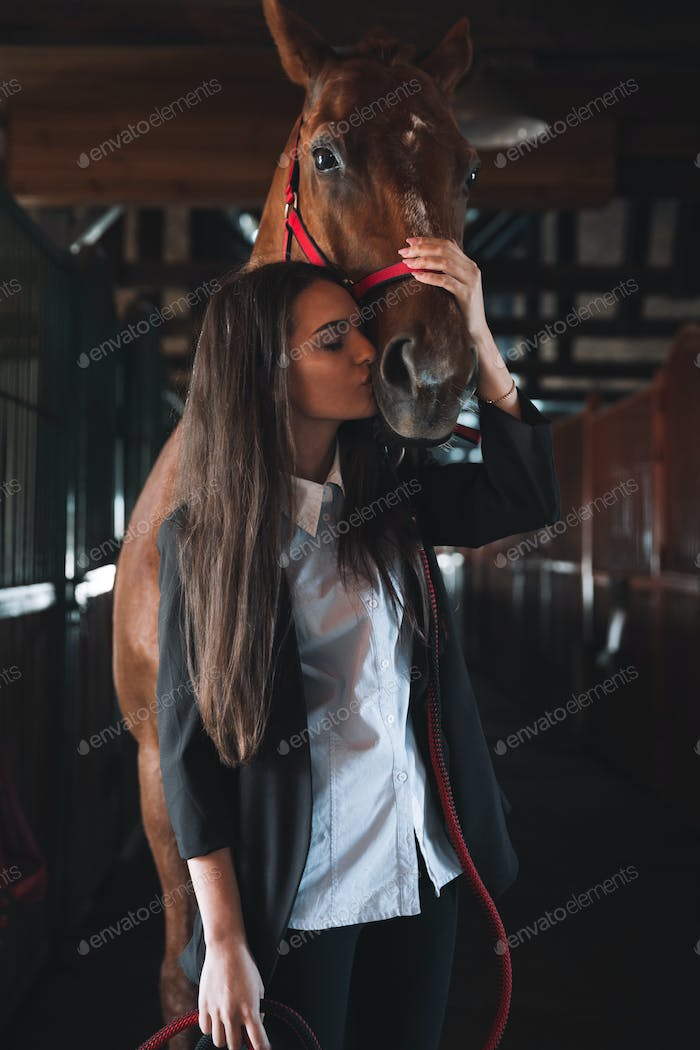 Amazing young woman standing in barn kissing her horse