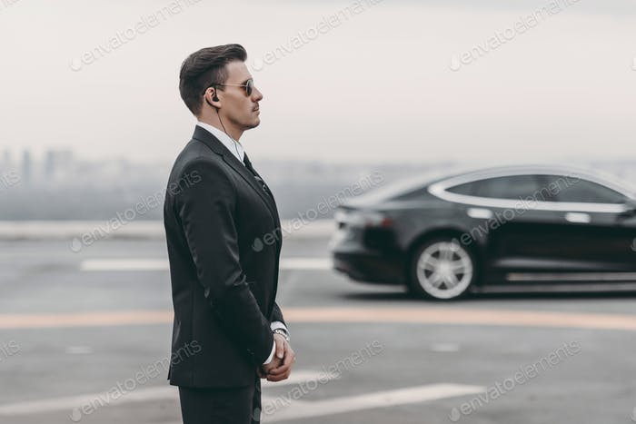 bodyguard in suit with security earpiece standing close to politician car