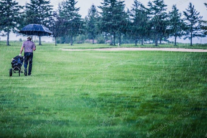Golfer an einem regnerischen Tag Verlassen des Golfplatzes