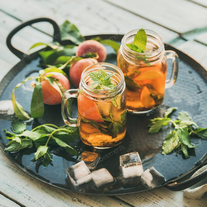 Summer refreshing cold peach ice tea on tray, square crop