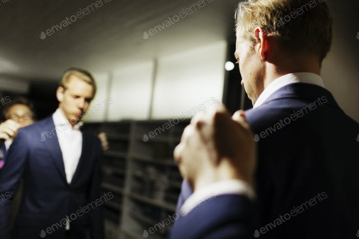 Sales clerk adjusting customer's suit in front of mirror at clothing store