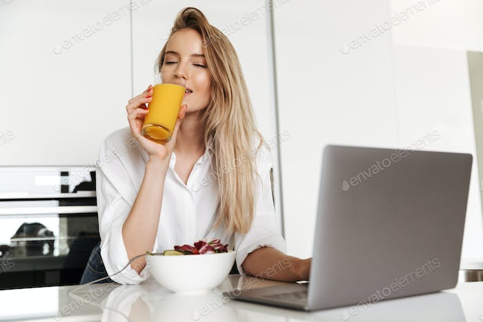 Delighted young woman eating salad