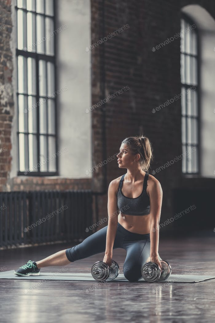 Athletic girl with dumbbells indoors