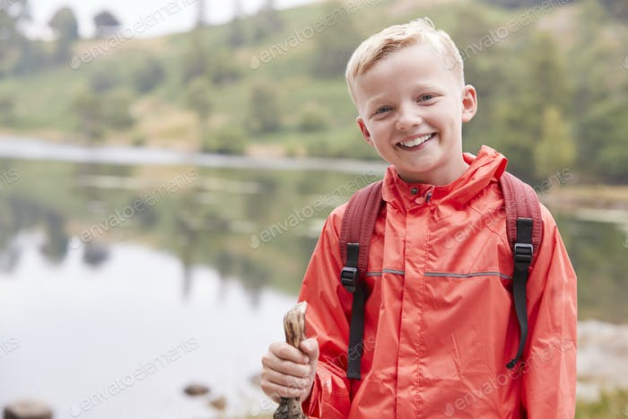 A pre-teen boy standing on the shore of a lake, looking to camera
