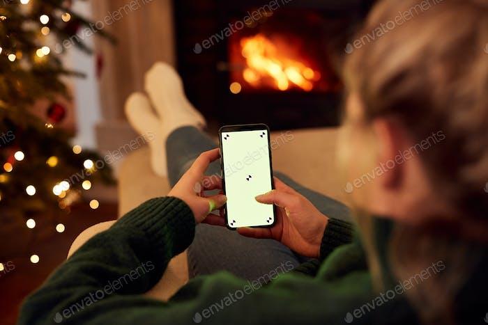 Frau zu Hause mit Handy mit leerer Bildschirm zu Weihnachten