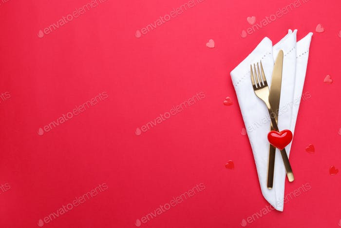 Gold cutlery on the red table cloth